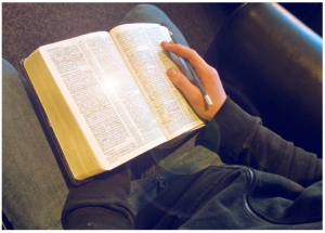 reading Bible in chair